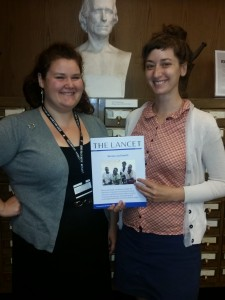 "Archivists Joan Ilacqua and Heather Mumford with a copy of The Lancet's report ""Women and Health: the key for sustainable development."""