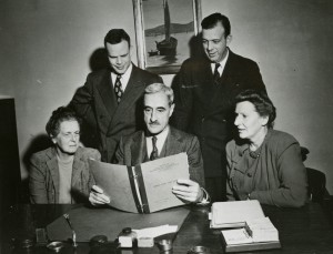 Faculty members of the Harvard School of Public Health Department of Maternal and Child Health, reading a Growth Study Case History. Seated: Bertha S. Burke, Harold C. Stuart, and Elizabeth P. Rice. Standing: Samuel W. Dooley and Samuel B. Kirkwood, circa 1949.