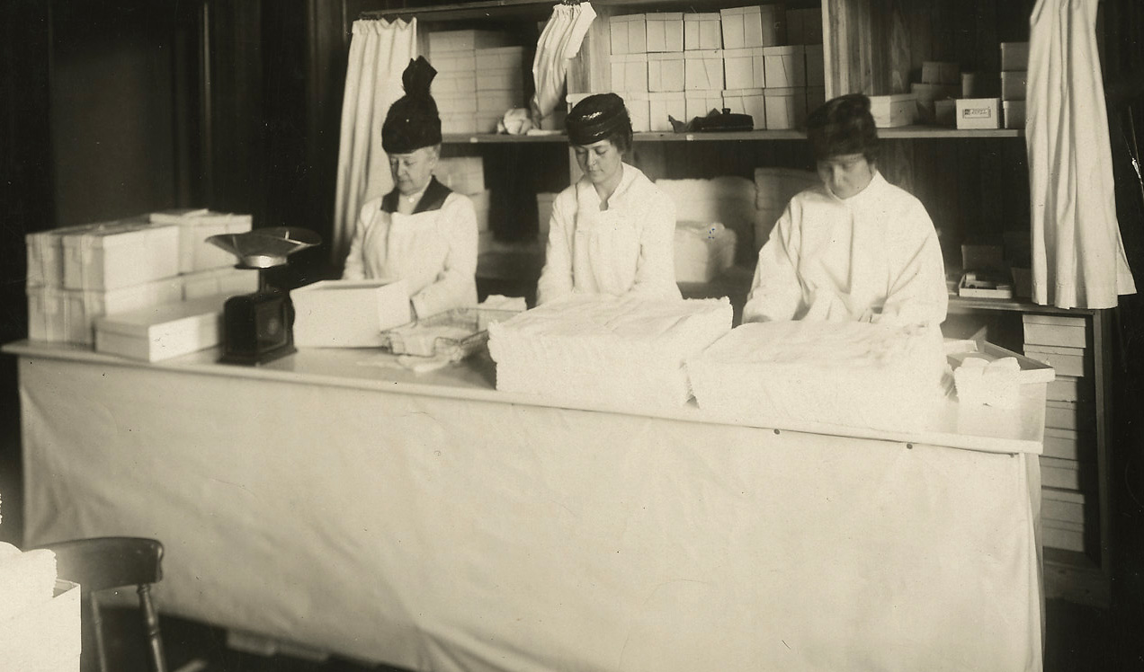 "Brigham and Women's Hospital Archives, BWH c3, Peter Bent Brigham Hospital Records. Volunteer workers in the Home Work Department of the New England Surgical Dressings Committee workrooms at 238 Beacon St. (Residence of Mrs. L. Carteret Fenno). Left to right: Miss Elizabeth Train, Mrs. Hatherly Foster, Jr., Mrs. Charles Rowley. [Photo is stamped with date ""MAR 17 1918"". Photo purchased for BWH archives from Historic Images, Memphis Tennessee, via eBay.]"