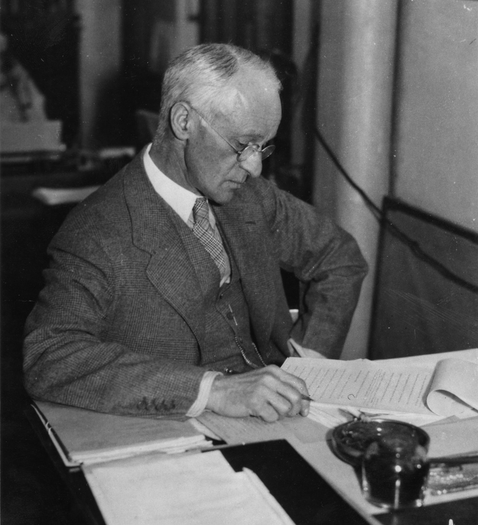 """1933. Boston, Mass. P.B.B.H. Dr. Cushing at the desk in the south office room."" Harvey Cushing at his desk in his post-retirement office. Photographer: Richard Upjohn Light"