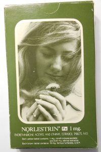 Cover of an instructional booklet for a brand of birth control pills. The cover has a picture of a woman looking down at a flower. She is wearing a wedding ring.